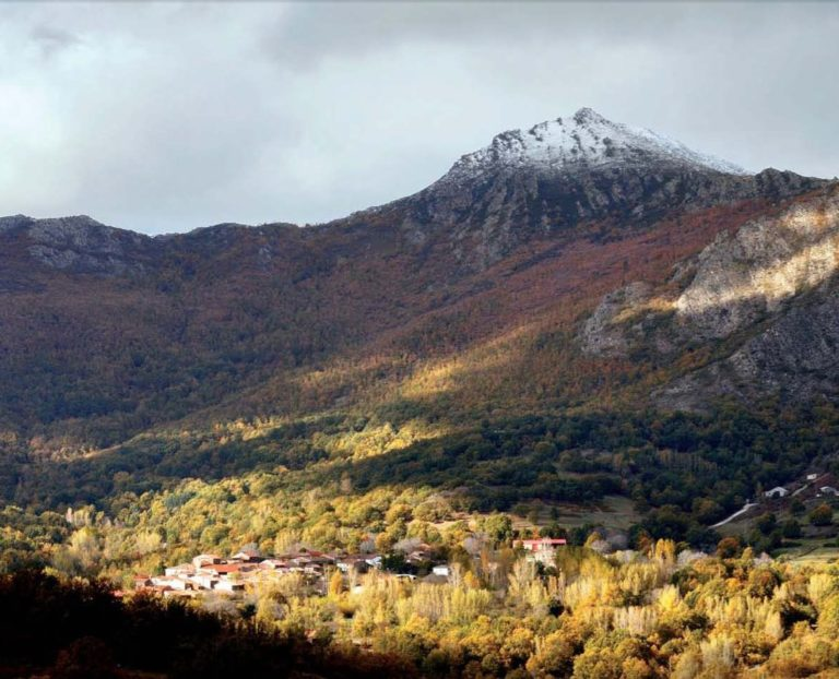 The village of Molinos de la Hiruela, surrounded by deciduous nacelles for autumnal polychromies, with the Pico de Sanuy, enraged with the first snowstorms of the year. Sierra del Rincón Biosphere Reserve, central Spain.